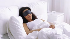 African woman with sleeping mask in bed at home Stock Footage