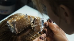 Hairdresser separating hair of the blonde Stock Footage