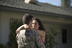 Male soldier hugging wife in garden on homecoming Stock Photos
