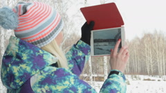 Girl with pad making photos of winter wood Stock Footage