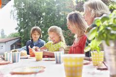 Girl opening birthday gift with her family at birthday party Stock Photos