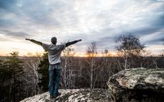 Young man with arms outstretched on top of rock formation at sunset Stock Photos