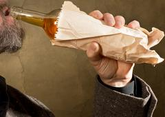 Hard drinker with a bottle in the paper bag Stock Photos