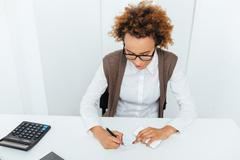 Curly african young woman accountant sitting and writing in office Stock Photos