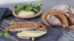 Dolly shot of cut sourdough bread and artisan cheese - stock footage