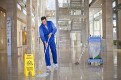 Male cleaner mopping in office atrium - stock photo