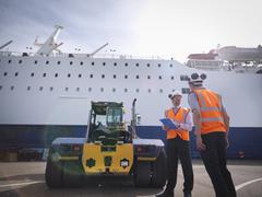 Port workers, shipping container truck and ship in port - stock photo