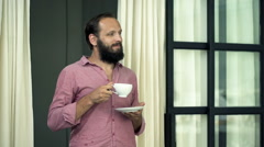 Young, happy man drinking coffee standing by room door Stock Footage
