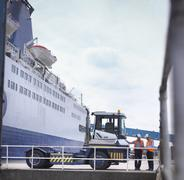 Port workers with shipping container truck and ship in port - stock photo