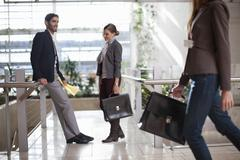 Businessman and businesswomen with briefcases in conference centre atrium - stock photo