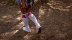 Sexy young woman in knee-highs walking Stock Footage