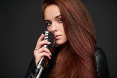 Closeup of young woman with retro microphone Kuvituskuvat