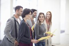 Row of businesswomen and men with paperwork in conference centre atrium Stock Photos