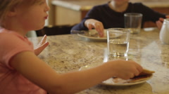 Brother and sister sharing pancakes and eating with their hands Stock Footage
