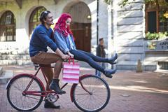 Young woman with sitting on boyfriends bicycle handlebars, Cape Town, South - stock photo