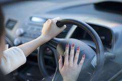 Cropped view of young businesswoman's hands pressing car horn - stock photo