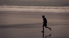 Silhouette of man jogging on beach, super slow motion 120fps - stock footage