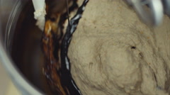 Adding melted chocolate into mixing dough - stock footage