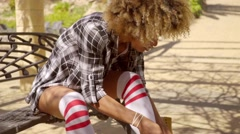 Young woman lacing up her roller skates Stock Footage