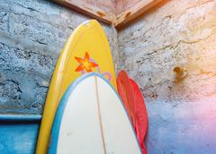 Paddles-boards with oars stand upright in the corner under the roof for renta - stock photo