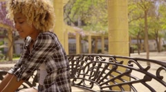 Young Woman Leaning Forward on Metal Bench Stock Footage