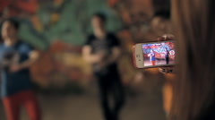 A girl is filming a break dance on her smartphone Stock Footage