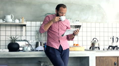Young man reading newspaper and drinking coffee in kitchen at home Stock Footage
