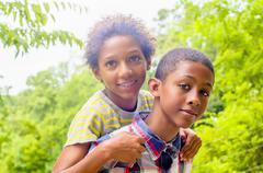 Close up of teenage boy giving friend piggyback ride Stock Photos