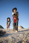 Low angle view of two brothers dressed as cowboys with hobby horses in sand Stock Photos