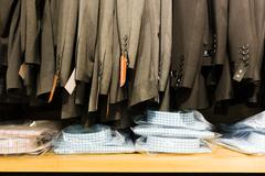 Row of sale suit jackets in men's clothes shop Stock Photos