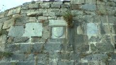 Heraldic Greek emblem in the wall of an ancient fortress. - stock footage