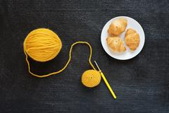 Yellow crocheting and croissants - stock photo