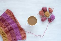 Cup of coffee and knitting on white background - stock photo