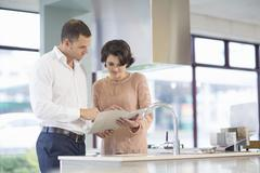 Female customer and salesman looking at brochure in kitchen showroom Stock Photos