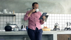 Young man reading news on tablet computer and drinking coffee in kitchen at home Stock Footage