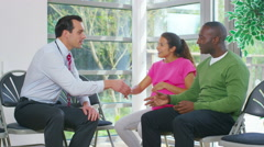 4K Friendly doctor talking to couple who are expecting a baby. Stock Footage