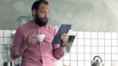 Young man reading shocking news on tablet computer and drinking coffee in kitche - stock footage