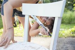 Mid adult woman bending forward to paint and restore chair in garden - stock photo