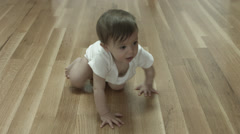 A baby crawling across a wooden floor wearing a onesie Stock Footage