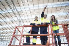 Low angle view of site managers and architect pointing from viewing platform on - stock photo