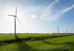 Row of wind turbines in front of sunrise in field landscape, Rilland, Zeeland, Stock Photos