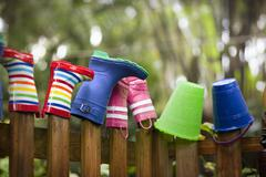 Row of rubber boots and buckets on top of garden fence Stock Photos