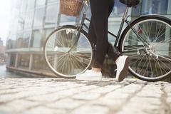Woman pushing bike along canal - stock photo