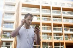 Man listening to music on headphones, building in background Stock Photos