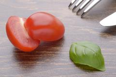 Halved cherry tomatoes and basil leaves on a dark table. Fork and knife. - stock photo