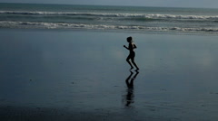 Silhouette of woman jogging on beach, super slow motion 240fps - stock footage