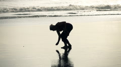 Silhouette of woman picking up seashell on beach, super slow motion 240fps - stock footage