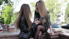 Two young women in the city are looking at the screen of a tablet, touching t Stock Footage