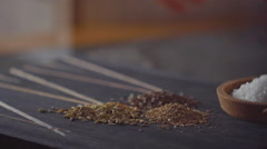 Slow dolly shot of a female putting seeds into stone mill and grinding them Stock Footage