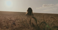 silhouette shot of a girl in a wheat field -  rising hands in happiness  - stock footage